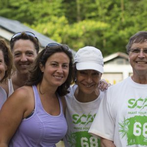 Group of adults smile while wearing SCAR branded shirts