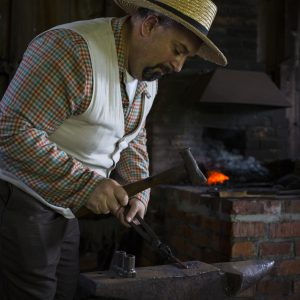 A volunteer in period costume blacksmiths at the John R. Park Homestead.
