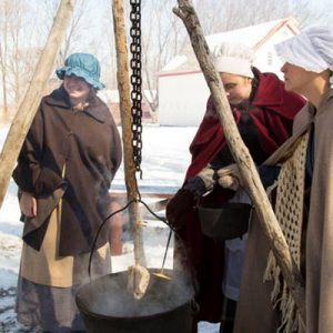 Reenactors making maple syrup in the snow