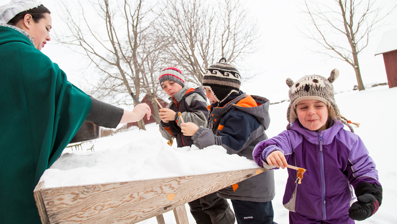 Children tasting maple syrup in the snow