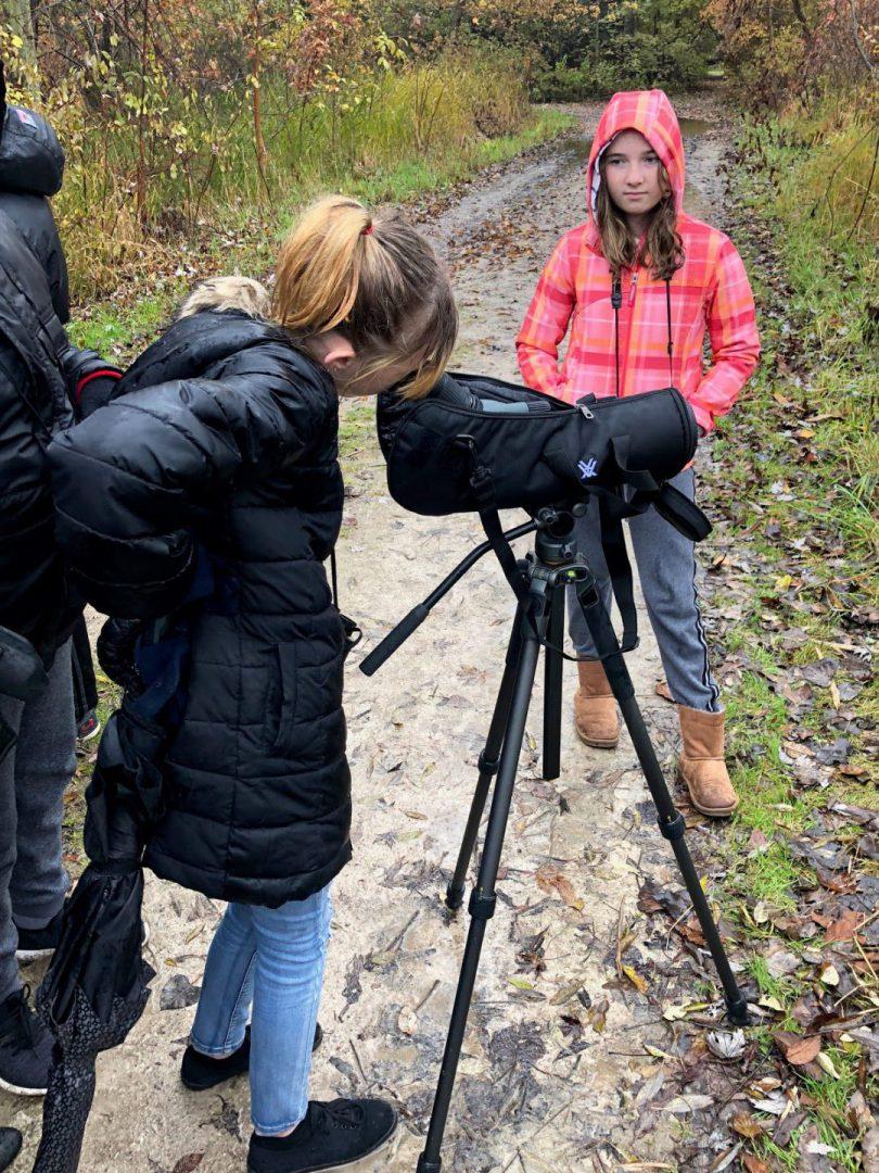 Pa student looking through binoculars