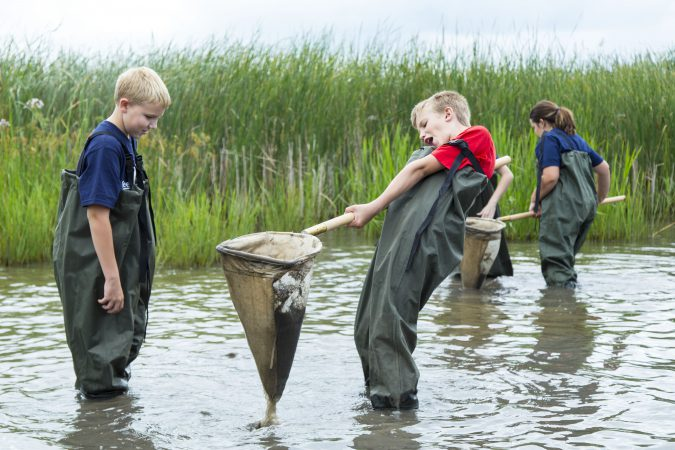 students dipnetting in a river