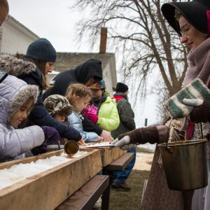 Guests at the Homestead tasting maple syrup