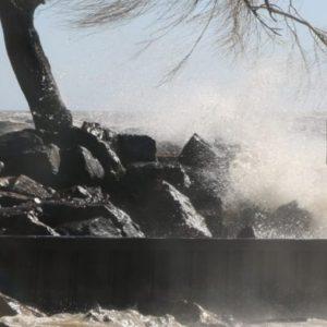 Waves-crashing-on-breakwall-with-house