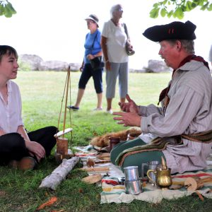 A Voyageur talking to a guest at the Homestead