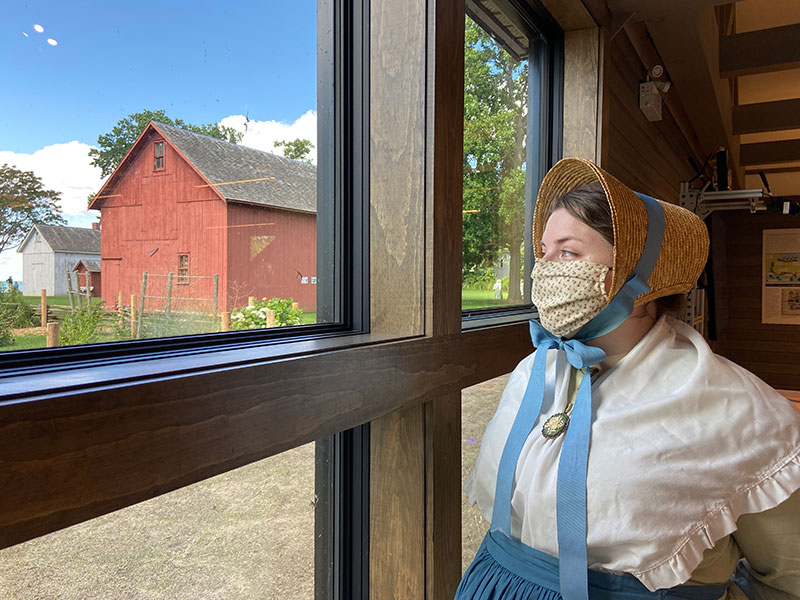 An interpreter in pioneer clothing looks out of a window