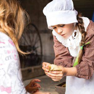 a reenactor makes a corn husk doll