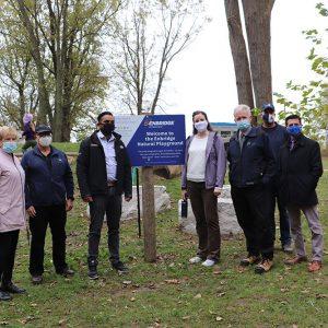 dignitaries pose next to the Enbridge Natural Playground sign